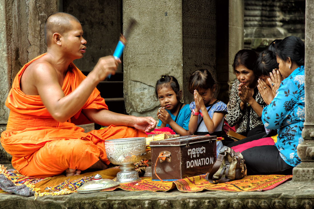 A monk prays with devotees, Angkor Wat, Siem Reap Cambodia