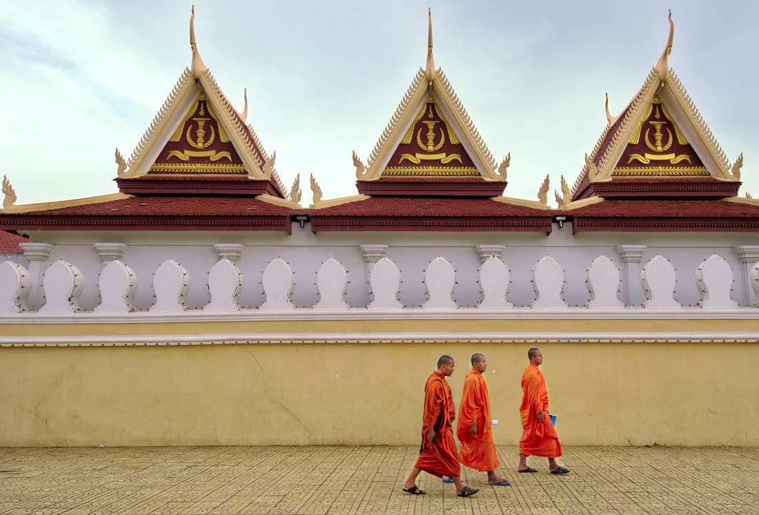 Monks stroll past the Royal Palace, Phnom Penh cambodia