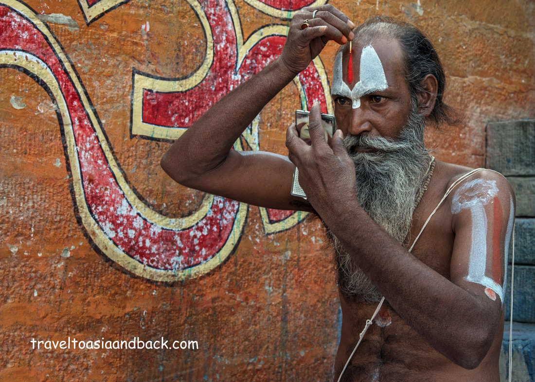 traveltoasiaandback.com - A sadu, or holy man, applies vermilion paste to his forehead