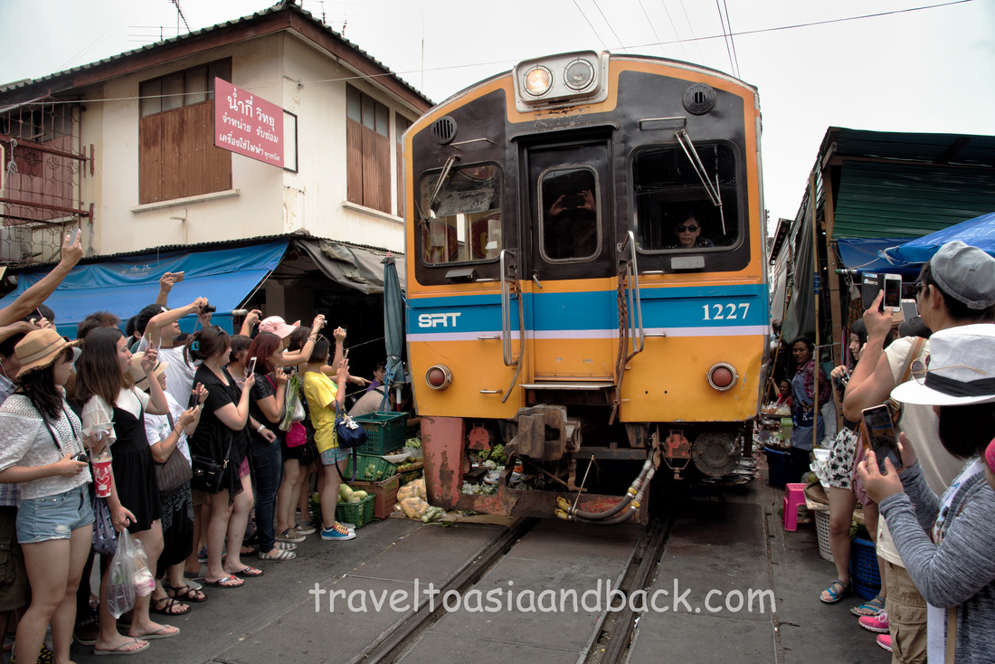 A train passes through the Maeklong Railway market, Samut Songkhram Province Thailand